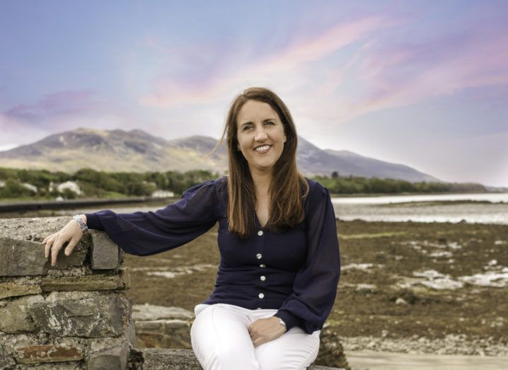 Payslip's Fidelma McGuirk sits on a wall, with a mountain and a sunset in the background.