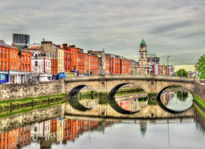 A picturesque view of the River Liffey down the centre of Dublin city with a bridge across the middle, which reflects perfectly in the river.