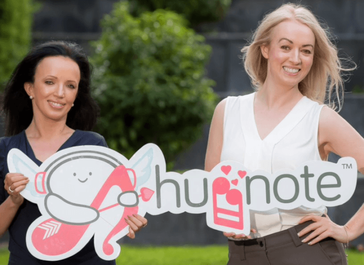 Huggnote co-founders Perry and Jacqui Meskell holding a sign of the company's logo.