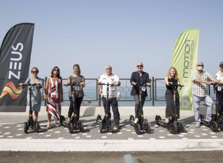 Teams from e-scooter company Zeus and Green Motion are pictured at Zeus's Italian launch in the coastal town of Anzio, with a blue sky in the background.