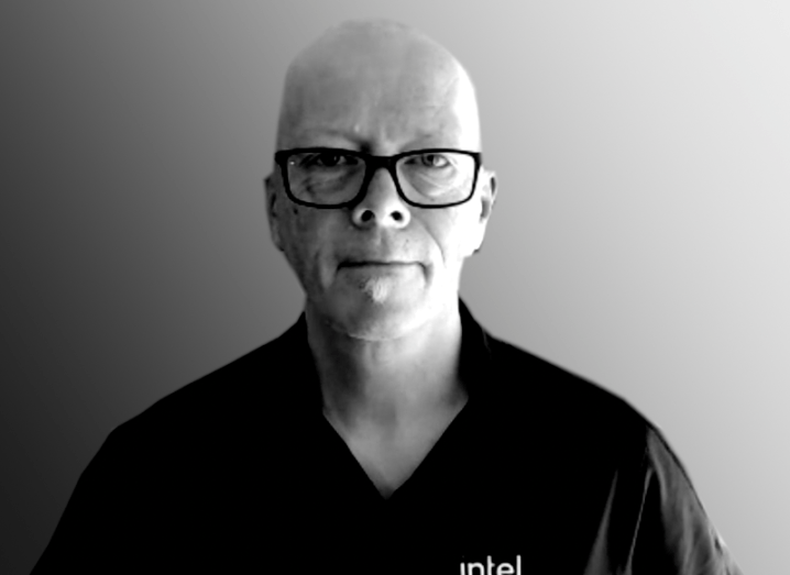 A black and white photo of Paul O'Neill, wearing a polo shirt with the Intel logo on it.