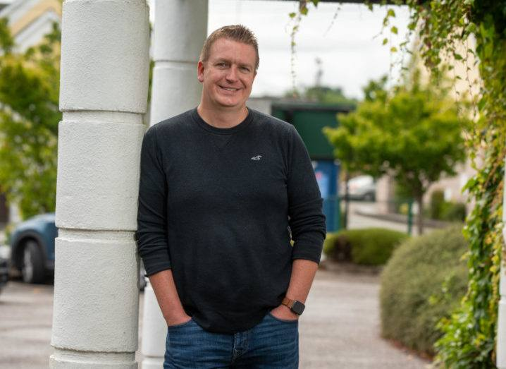 A man wearing a dark jumper with his hands in his pockets standing outside with trees in the background. He's smiling at the camera.