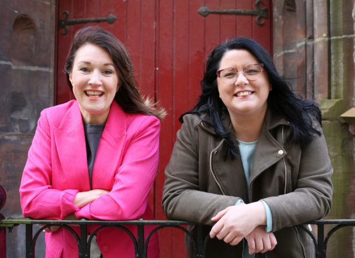 Jennifer Neff and Leann Monk-Özgül, founders of Elemental Software, pictured side by side, smiling and leaning on some railings outside a building.