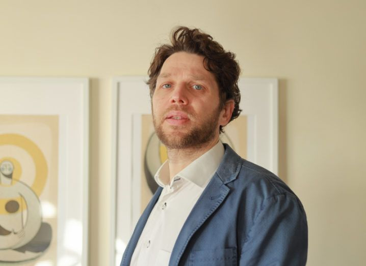 Dr Matteo Lusi, wearing a white shirt and blue-grey blazer, standing against a cream-coloured wall bearing two abstract paintings in neutral tones.