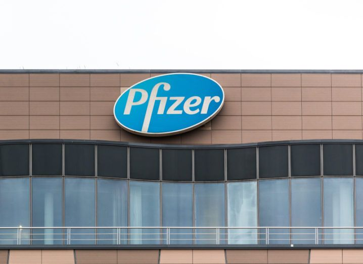 The Pfizer logo on the top of a brown office building against a bright white sky.