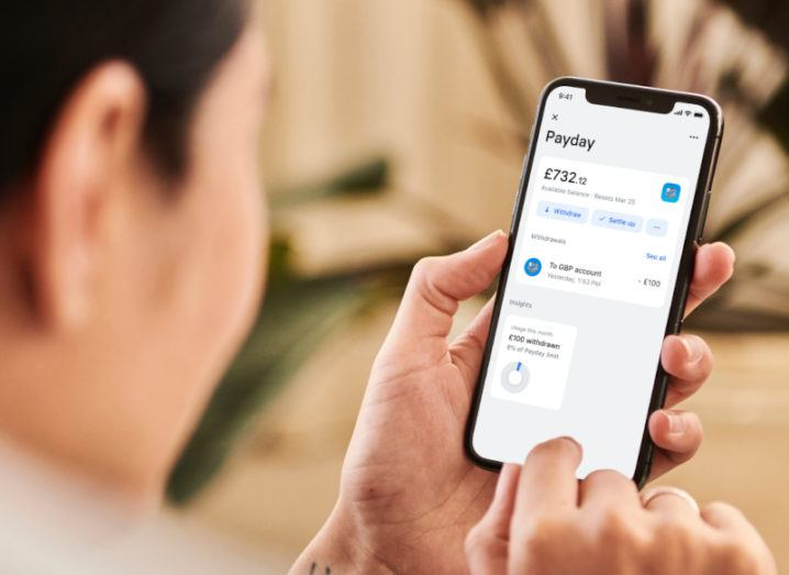 A promotional image showing someone looking at the Payday feature on the Revolut app on a phone.