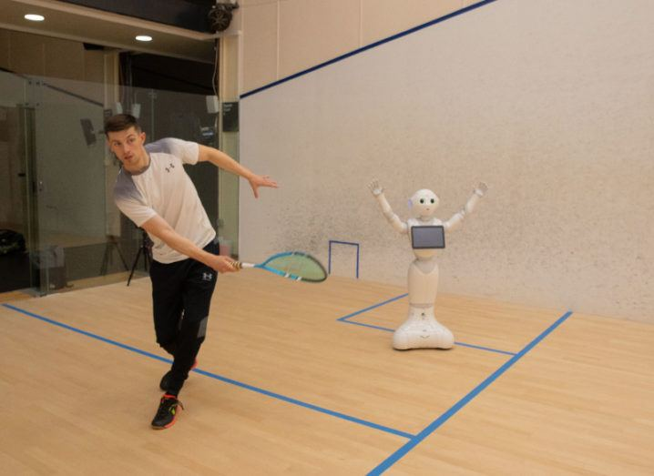 The robot coach is pictured beside a man practicing squash. The man is mid-swing with a racket in his hand. The robot squash coach has his arms in the air and looks to be celebrating a good swing. The robot is approximately a metre tall and is humanoid in appearance. It has a screen on its chest to act as an interface.