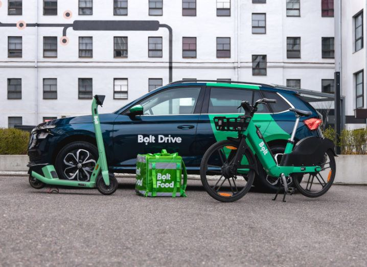 A promotional image of a car from Bolt's Bolt Drive service, a Bolt e-scooter, a Bolt Food delivery bag, and a Bolt e-bike.