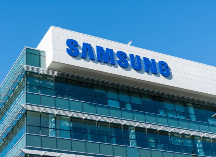 The blue Samsung logo at the top of a large glass office building against a blue sky.
