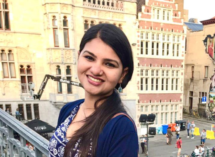 Dr Shalini Singh pictured on a balcony overlooking a plaza in a European city, surrounded by historic buildings.