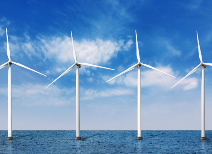 Photo of floating wind turbines under a blue sky.