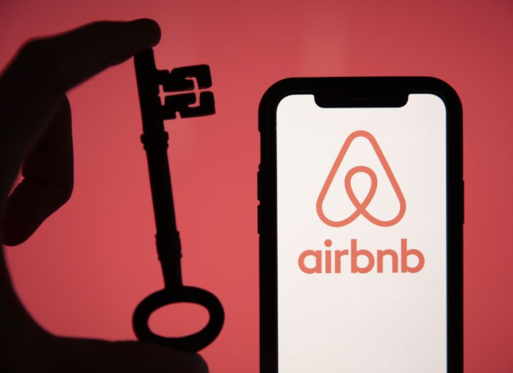 Airbnb logo on a smartphone and hand holding a key in the backdrop.