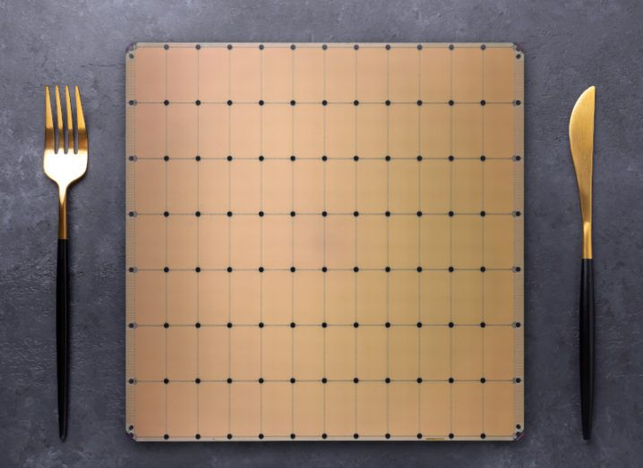 The Cerebras WSE-2 chip is shown on a dinner table. It is a bronze colour with a black dot grid. There is a bronze knife and fork on either side of the chip.