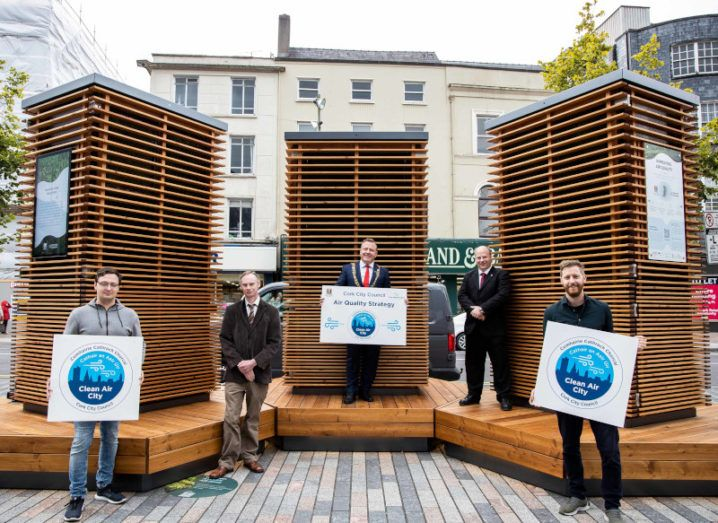 Four men standing in front of the CityTree units in Cork's city centre. Three of them are holding signs.