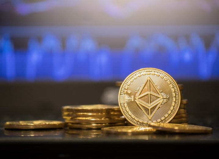 An Ethereum bold coin stands up beside a stack of other cryptocurrency coins against a blurred out blue line graph.