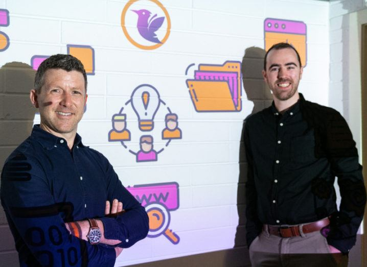 Olus Education chief product officer Gavin Molloy and CEO Diarmuid Ó Muirgheasa pictured at the company launch at Dublin's Digital Hub standing against a whiteboard decorated with education symbols.