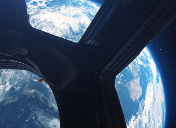 The Earth is pictured from inside the International Space Station. The curve of the Earth can be seen and glows brightly against the darkness of space.