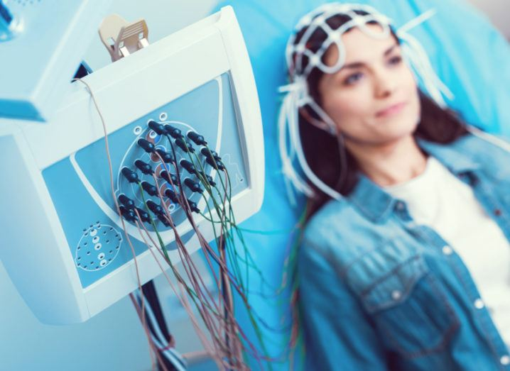 A woman is sitting in a chair connected to an EEG machine. The EEG machine is in focus at the front of the shot, while she is in the background. She is wearing a white T-shirt and a denim jacket and has long, brown hair.