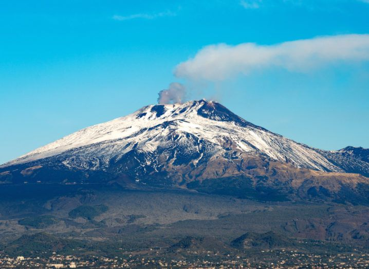 The city of Catania can be seen at the base of Mount Etna. Smoke is rising from a crater of Etna, showing that its volcanic activity is ongoing. The sky is a clear and a light blue colour.