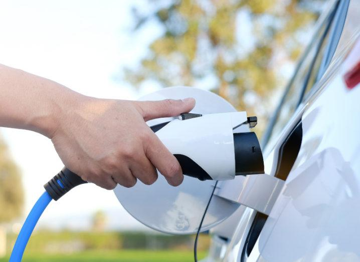 A person's hand is plugging a charger into an EV.