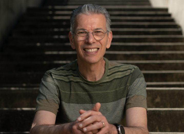 Photo of David Feinberg seated on a flight of stairs and smiling.