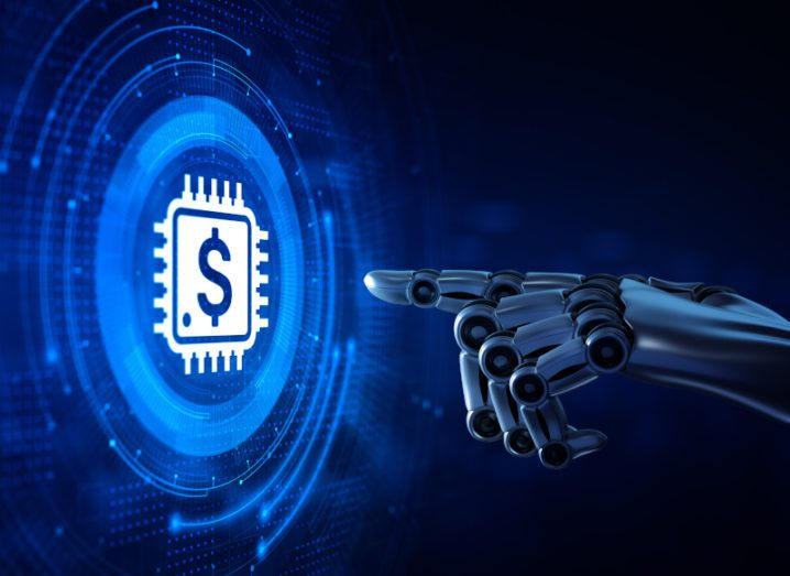 A robotic hand is pointing at a glowing image of a chip that has a dollar sign on it.