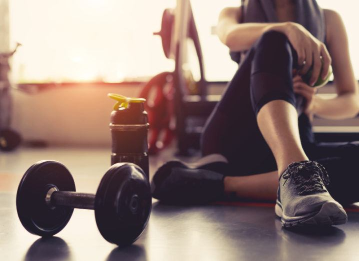A person is pictured in the gym. They are sitting on the ground with one arm on their knee. There is a dumbbell and other gym equipment around them.
