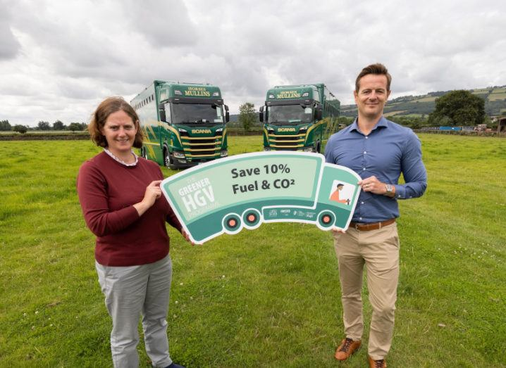 Alexandra Hamilton and Robert Steele are smiling and holding a truck-shaped sign for the Greener HGV programme. The sign says save 10pc fuel and CO2. They are both smiling and there are two large green trucks in the background.