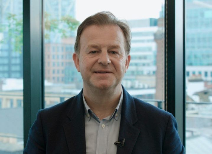 Headshot of Derek Stewart, CEO and founder of Paysme taken against a window with a view of office buildings in the background.