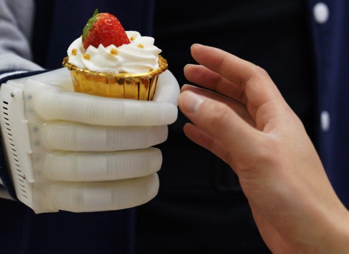 The prosthetic limb is reaching out with a cupcake in its grasp. Another human hand is leaning forward to take the cupcake. The material of the artificial hand is soft and has visible ridges, but is firmly grasping the cake.