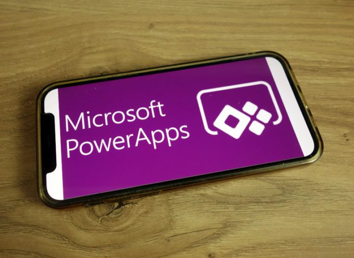 Microsoft Powers Apps logo on a smartphone.