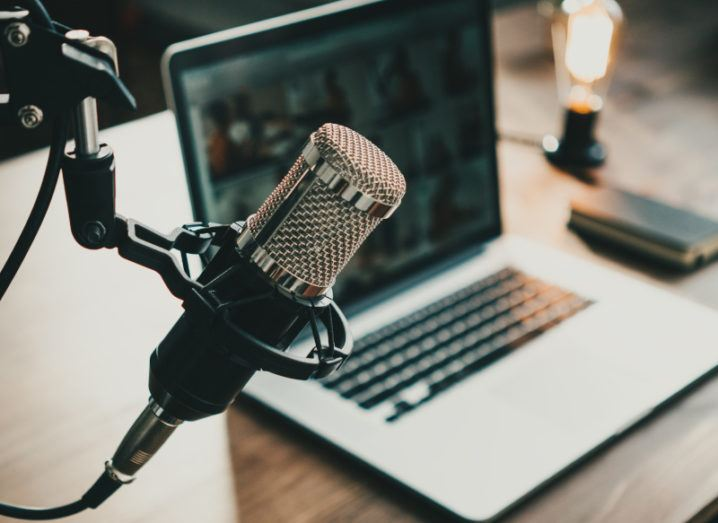 A professional looking microphone sits above a laptop at a desk.