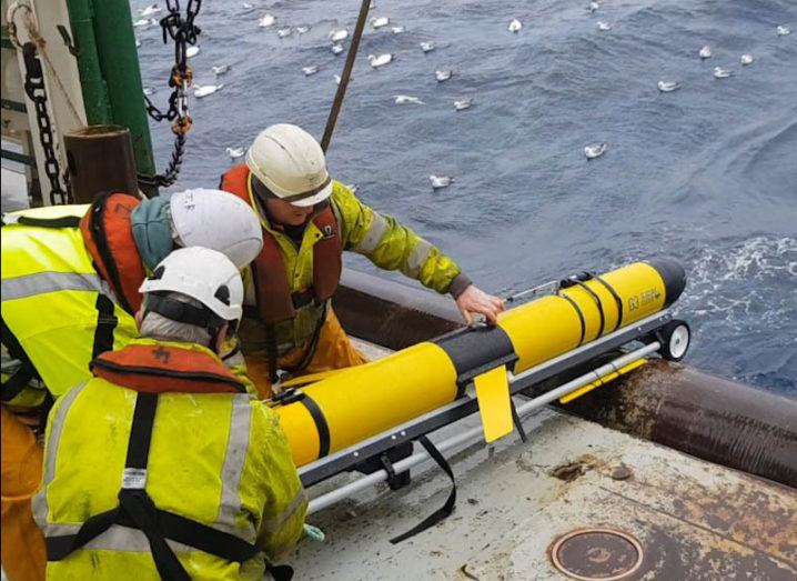The ocean glider is being deployed by three people from a boat. The glider is a large, yellow tube that is angled towards the water. The people are wearing yellow overalls with life-preserver jackets over them. There are many seagulls in the water.