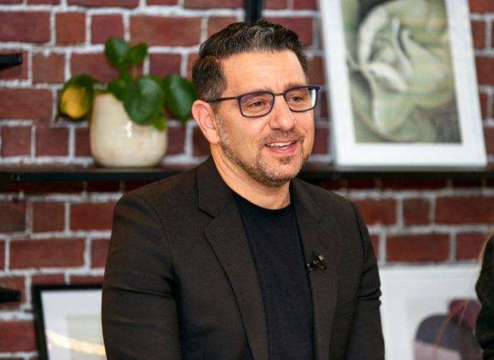 Photo of Panos Panay sitting in a dark suit in a casual office space.