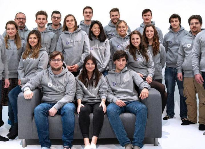 The staff of Refurbed posing for a group photo in hoodies branded with the start-up's logo.
