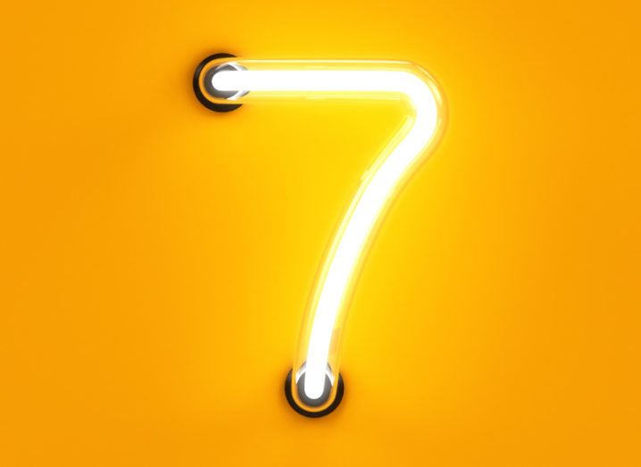A neon light in the shape of the number seven lit up against a yellow background.