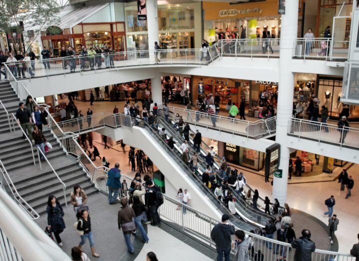 A busy shopping centre is pictured. Three stories of the shopping centre are visible and there are people outside of all the shops. There is an escalator and a staircase going between each of the levels.