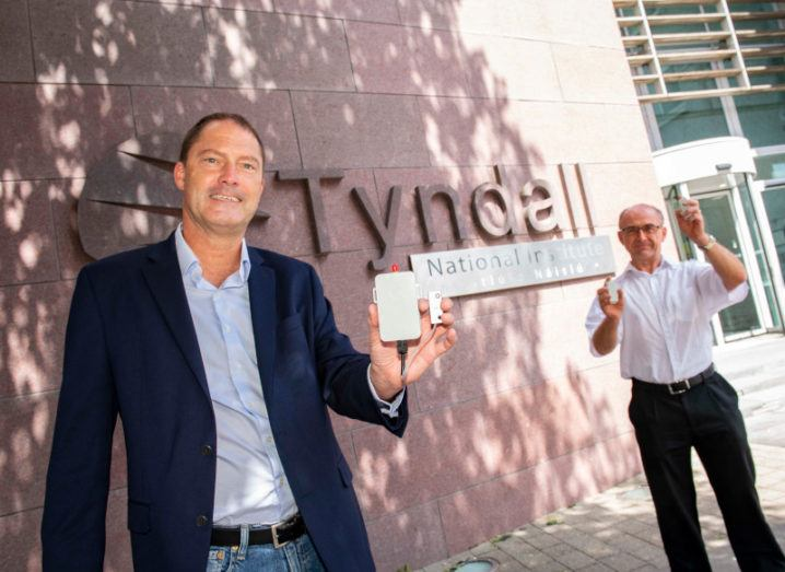 Mike Fitzgerald and Mike Hayes are standing outside the building of the Tyndall National Institute. Fitzgerald is on the left and is holding the smart cargo sensor in his left hand. Hayes is further back on the right and is holding a sensor in each hand. Both men are smiling and looking at the camera.