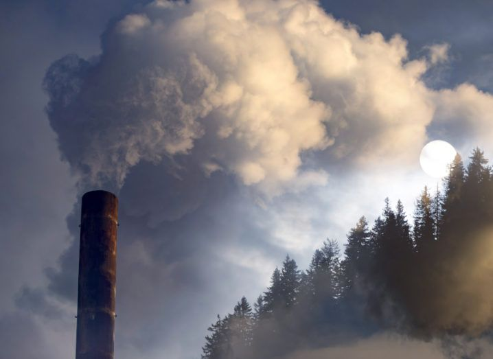 A tower is pictured billowing smoke into the air. The smoke is travelling into a forest of trees, showing the company's negative impact on the environment.