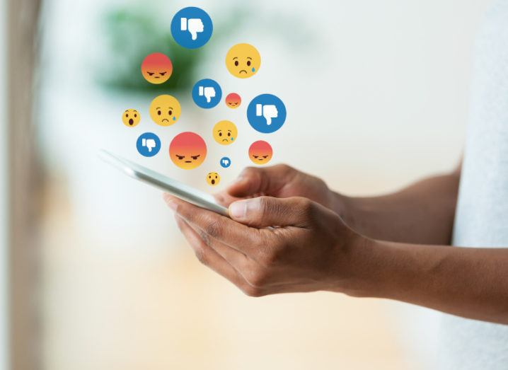Someone is holding a smartphone in their hands. Moral outrage is shown coming from the phone as angry and sad emojis are shown rising from the phones screen. Only the person's hands are in the shot of the photo.