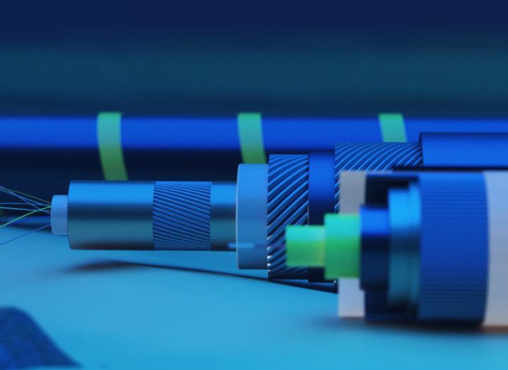 A 3D rendering of a blue and green subsea cable lying on the ocean floor.