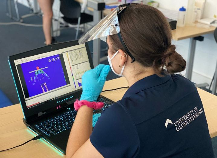 A woman is sitting at her laptop analysing outputs from the sports trials. It shows the properties of the graphene sportswear.