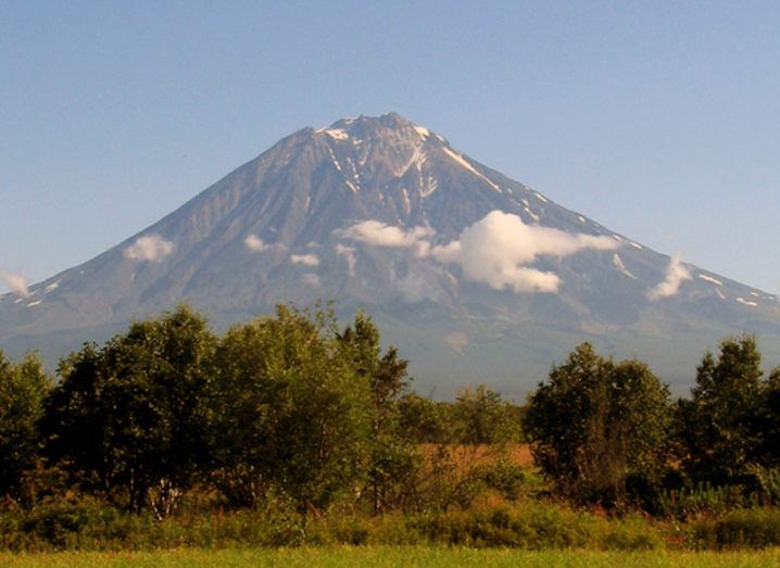 A volcano in the Kamchatka Peninsula is pictured. The volcano is in the distance from the photographer, who is in a field. There are some cirrus clouds visible halfway up the volcano but otherwise the sky is clear. There are some trees between the photographer and the base of the volcano, obscuring the view.