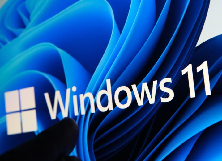 Windows 11 logo in white with a blue patterned background.