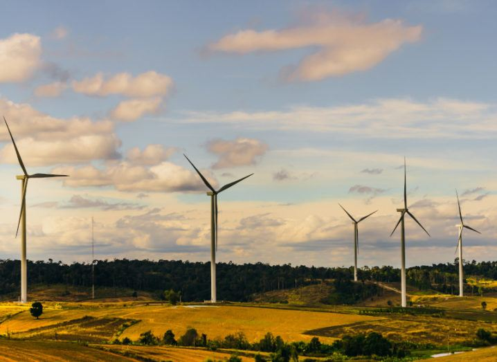 Several wind turbines dotted across wide, rolling fields on a bright day. There are white, fluffy clouds in a blue sky.