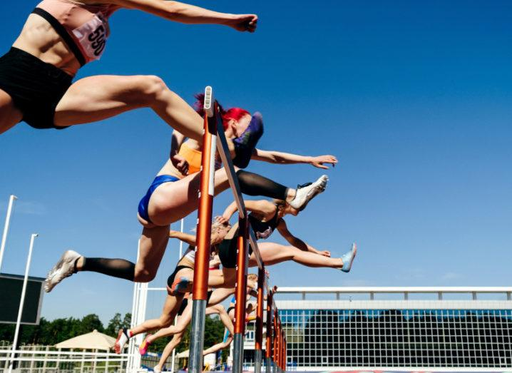 Women are pictured mid-jump in the 100-metre hurdles race.