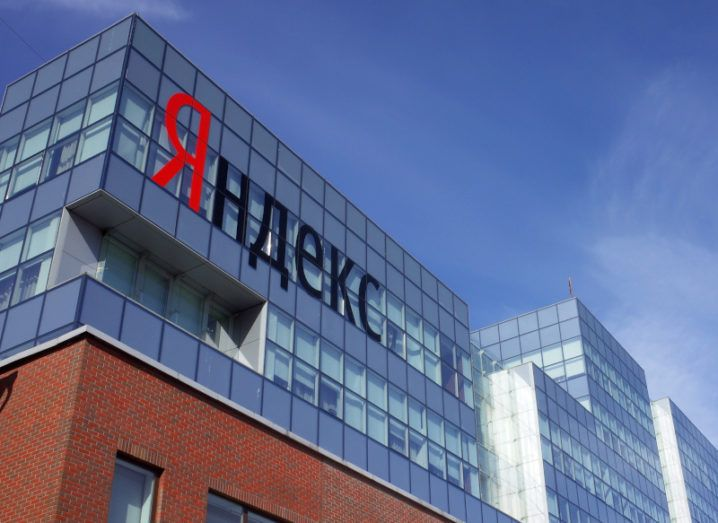 A Yandex office building is pictured from the street. The Yandex branding is visible on the side of the building.