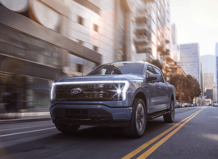 The 2022 Ford F-150 Lightning electric truck driving down a city street.