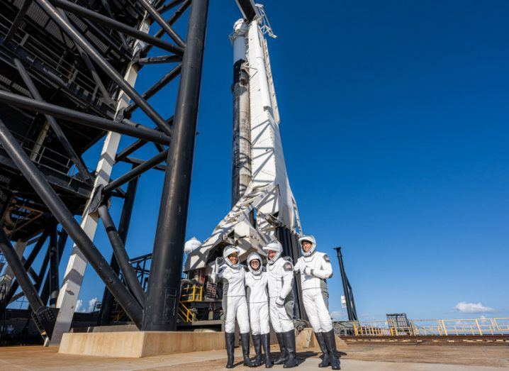 Four people in space suits stand in front of a large white rocket against a bright blue sky.