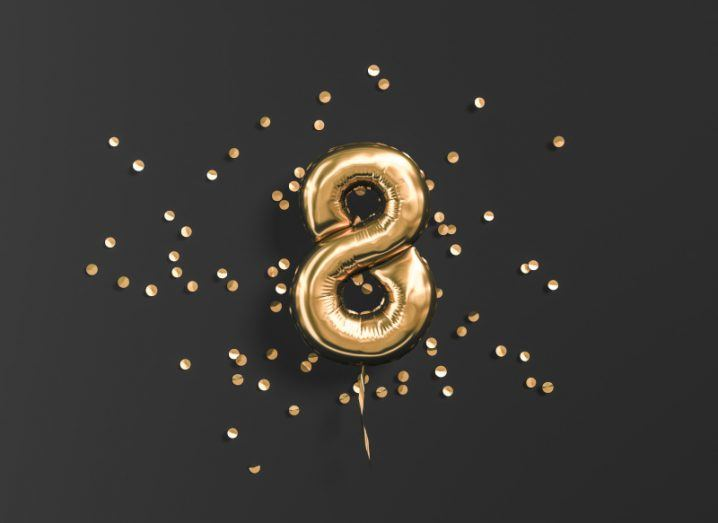 Number eight shaped golden balloon with gold confetti in a black background.